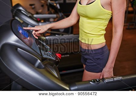 Fit girl in activewear training on sportive equipment