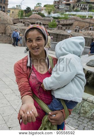 TBILISI, GEORGIA - MAY 02, 2015: Unknown woman with a child in her arms begging.