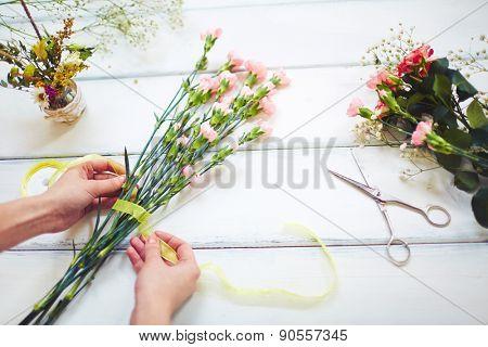 Female hands tying pink carnation bouquet