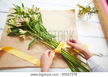Female florist tying up fresh bouquet with yellow ribbon