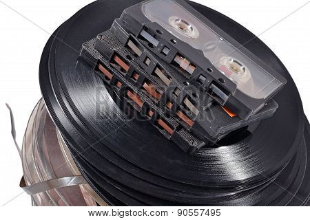 Old Vintage Bobbins, Vinyl Records And Cassette Tapes On A White