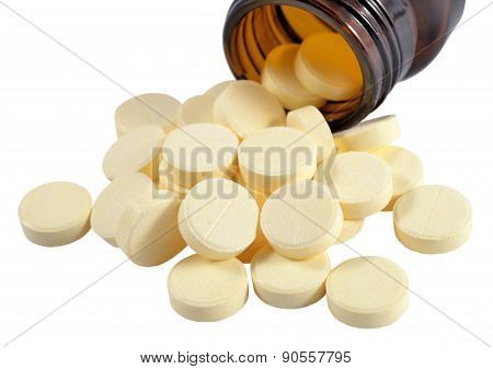Pills Spill Out From Bottle On A White