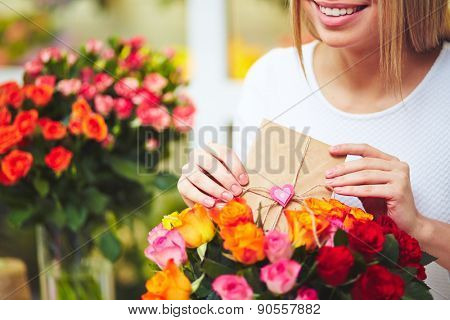 Smiling florist putting message for receiver in rose bouquet