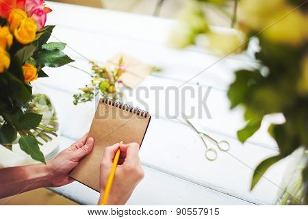 Florist with pencil making notes in notepad over workplace