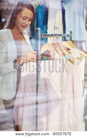 Young shopper looking through new clothes