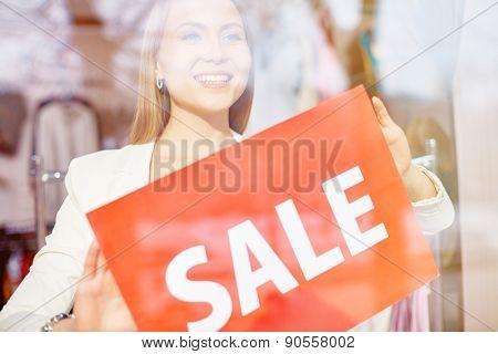 Beautiful shop assistant announcing sale season