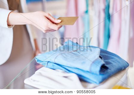 Shopper giving plastic card to assistant over chosen clothes
