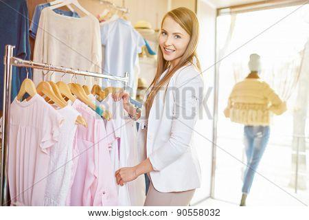 Beautiful young woman choosing new dress in boutique