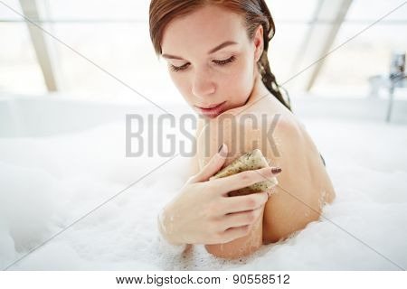 Young woman exfoliating her skin with soap in bath