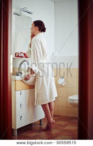 Relaxed female in bathrobe looking in mirror