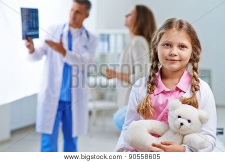 Sweet girl with white teddy looking at camera with her doctor talking to woman on background