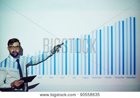 Male employee with touchpad explaining chart on the wall