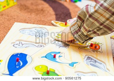 Little Child Puts The Simple Puzzle On The Floor