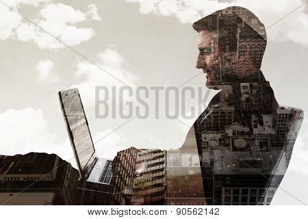 Businessman using laptop against low angle view of skyscrapers