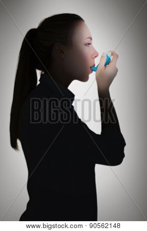 Beautiful blonde using an asthma inhaler against grey vignette