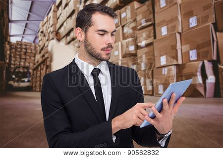 Cheerful businessman touching digital tablet against worker with fork pallet truck stacker in warehouse