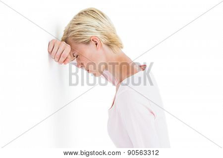 Nervous blonde woman leaning against the wall on white background