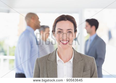Businesswoman smiling at camera while her colleagues discussing in the office