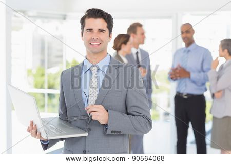Businessman with his laptop and his colleagues behind in the office