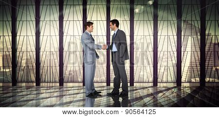 Businessmen shaking hands against room with large window looking on city