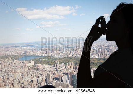 Asthmatic brunette using her inhaler against new york