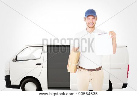 Happy delivery man holding cardboard box and clipboard against white delivery van