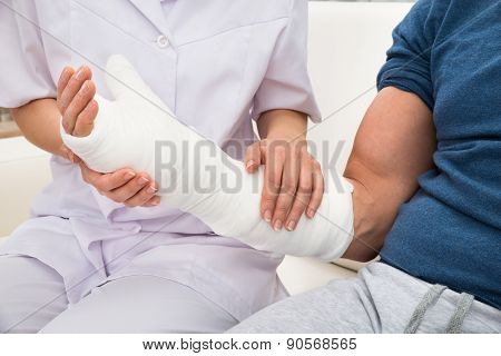 Female Doctor Holding Fractured Hand Of A Patient