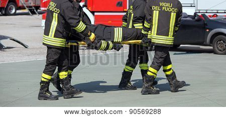 Brave Firefighters Carry A Fellow Firefighter With The Stretcher