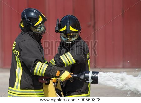 Two Firemen In Action With Foam