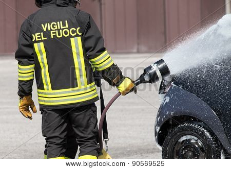 Firefighter In Action With Foam To Put Out The Fire