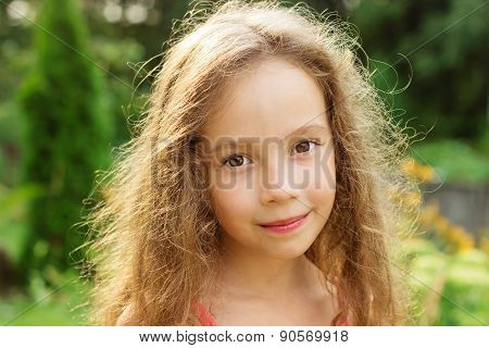 Cute smiling little girl on background of city park at summer