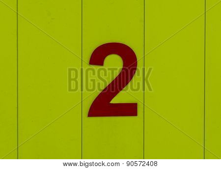The number two, red, set against bright yellow wood