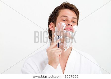 young man shaving in morning