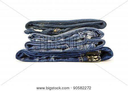 A Stack Of Denim Trousers On A White Background
