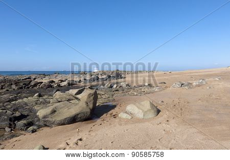 Rocks Exposed At Low Tide On Empty Beach