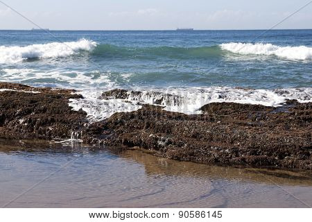 Waves Breaking Over Rocks Covered With Seaweed And Barnacles