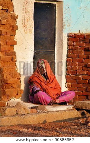 Indian Woman In Orange Sari Sits On A House Porch