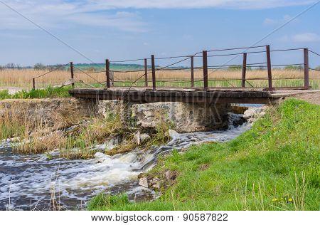 Old pedestrian bridge over small Ukrainian river Kilchen