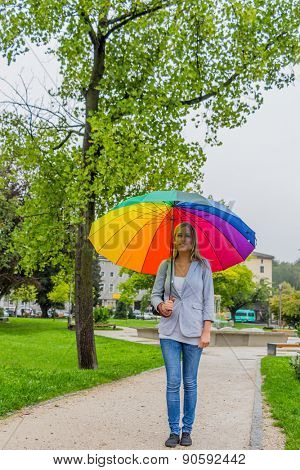 a young woman walks with a colorful umbrella in his hand walking in the rain.