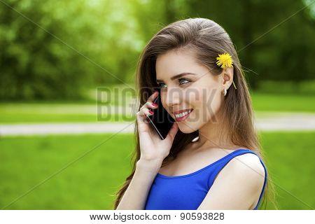 Happy beautiful brunette woman calling by phone in a summer park