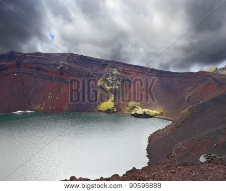Iceland in July. Oval blue lake in the crater of the volcano cooled down. The lake shores are made of red rhyolite