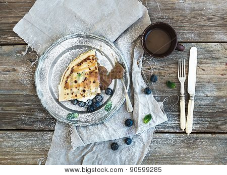 Thin pancake or crepe with fresh blueberry, cream, mint, and salty caramel sauce in vintage metal pl