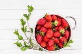 foto of mints  - Mint and strawberries in rustic colander on white wooden table - JPG