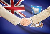 picture of falklands  - Businessmen shaking hands with flag on background  - JPG