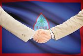 picture of guam  - Businessmen shaking hands with flag on background  - JPG