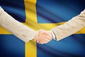 stock photo of sweden flag  - Businessmen shaking hands with flag on background  - JPG