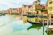 picture of gondola  - Beautiful colorful image of a canal in Venice with moorings and a gondola in the forefront and old houses under blue cloudy sky in the background - JPG