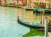 image of gondola  - Beautiful colorful image of a canal in Venice with moorings and a gondola in the forefront and old houses under blue cloudy sky in the background - JPG