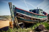 picture of old boat  - The remains of an old fishing boat rotting on the river shore - JPG
