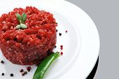 picture of hamburger-steak  - very big raw hamburger cutlet with sprouts and chilli pepper on white plate over black background - JPG